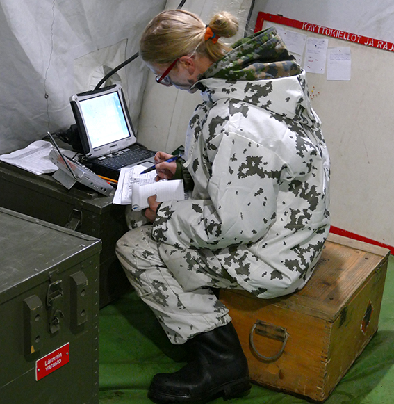 A female soldier writes notes from a computer