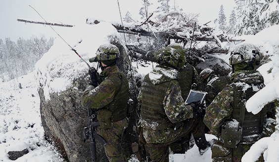 Soldiers in a snowy forest sheltered by large rocks